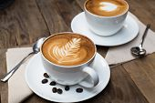 stock photo of latte  - Cup of hot latte art coffee on wooden table - JPG