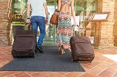 Young couple standing at hotel corridor upon arrival looking for room holding suitcases