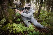 stock photo of paintball  - active paintball sport player in the forest with protective clothing - JPG