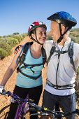 Active couple embracing on a bike ride in the country on a sunny day