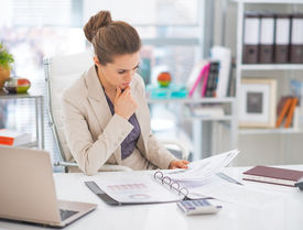 stock photo of thoughtfulness  - Thoughtful business woman documents in modern office - JPG