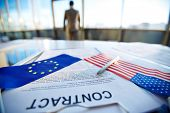 Business contract with pen, American flag and flag of European Union with male employee on background