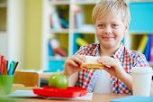 Smiling schoolboy with sandwich sitting at workplace