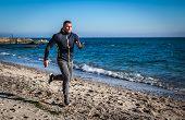 Running man jogging on beach.