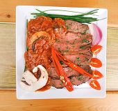 beef on plate with vegetables over wooden table