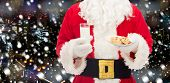 christmas, holidays, food, drink and people concept - close up of santa claus with glass of milk and cookies over snowy night city background