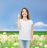 advertising, childhood, nature, gesture and people concept - smiling girl in white t-shirt pointing finger up over flower field background