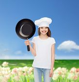 advertising, childhood, cooking and people concept - smiling girl in white t-shirt and cooking hat holding pan over flower field background