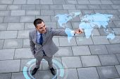 global business, development, technology and people and concept - young smiling businessman pointing finger to world map projection outdoors from top