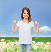 advertising, childhood, nature, gesture and people concept - smiling girl in white t-shirt pointing fingers on herself over field background