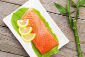 Fresh salmon fish with lemon and salad leaves on wooden table