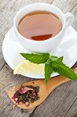 Green tea with lemon and mint on wooden table background