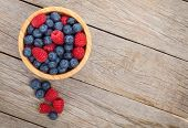 Blueberries and raspberries bowl on wooden table with copy space