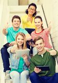 education and technology concept - smiling students with tablet pc computer sitting on staircase and showing thumbs up