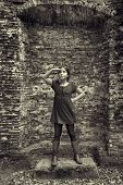 Teenage girl acting as a lady from the past standing in front of the ruin of her castle