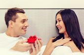 hotel, travel, relationships, holidays and happiness concept - man giving woman little red gift box