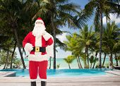 christmas, holidays, travel and people concept - man in costume of santa claus with bag over tropical beach and swimming pool background