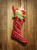 Christmas sock with red gift box on wooden background