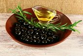 Saucepan and black olives with branch in brown bowl on painted wooden table, on burlap background