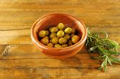 Green olives in the round bowl with branch on rustic wooden background