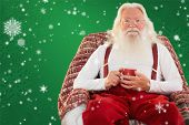 Father christmas sitting on the armchair holding mug against red background