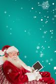 Father christmas listening to music with tablet against red background