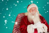 Portrait of father christmas sitting on the armchair against red background