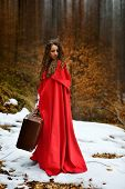 beautiful woman with red cloak and suitcase alone in the woods
