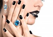 Closeup face of young beautiful woman with black manicure and fashion bright makeup.
