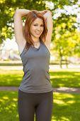 Portrait of a pretty redhead stretching on a sunny day
