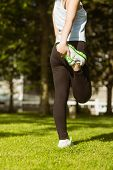 Rear view of healthy young woman stretching leg in park