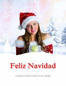 pretty girl in santa costume holding gift box against feliz navidad