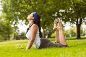 Calm brown hair doing yoga on grass in the park