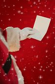 Father christmas holding a paper against red background