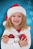 Festive little girl smiling at camera against snowflake pattern on blue planks