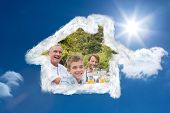 Laughing family having a barbecue in the park together against bright blue sky with clouds