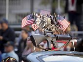 NEW YORK - NOV 11, 2014: A rifle along with American and POW/MIA flags mounted to the roof of a car participating in the 2014 Americas Parade on Veterans Day in New York City on November 11, 2014.