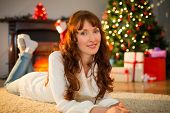 Smiling redhead woman lying on floor at christmas at home in the living room