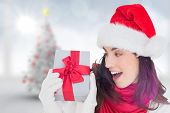 Astonished brunette in santa hat showing gift against blurry christmas tree in room