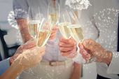 Hands toasting with champagne against white fireworks exploding on black background