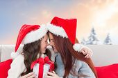 Mother and daughter with gift against blurred snowy landscape