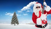 Santa with sunglasses playing electric guitar against fir tree in snowy landscape