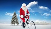 Cheerful father christmas cycling against fir tree in snowy landscape