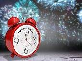 Happy new year in red alarm clock against bleached wooden planks background