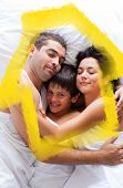 Happy family lying in bed against house outline in clouds