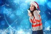 Happy brunette holding her cash against blurred christmas background