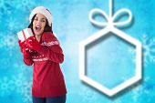 Excited brunette showing christmas present against blurred christmas background
