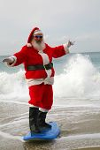 Surfing Santa Claus. Santa Claus rides on his surfboard as he rides the waves of the ocean blue. Santa Loves Sports the beach and the outdoors. Santa loves to surf on his surfboard as much as he can