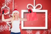 Festive blonde cheering with boxing gloves against blurred christmas background