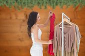 Woman choosing clothes against blurred fir tree branches on wood